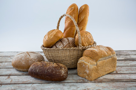 loaves: Various bread loaves on wooden surface against white background
