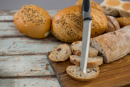 loaves: Various bread loaves with knife on wooden surface
