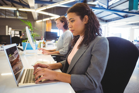 confident business woman: Attentive woman sitting at desk and working on laptop Stock Photo