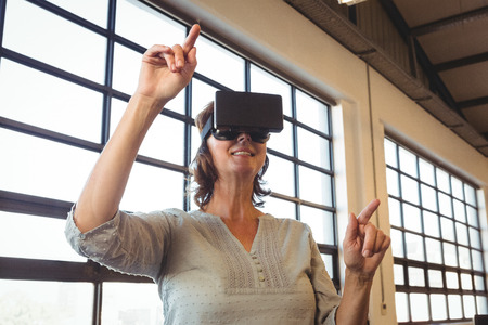 virtual office: Business executive wearing virtual reality headset in office