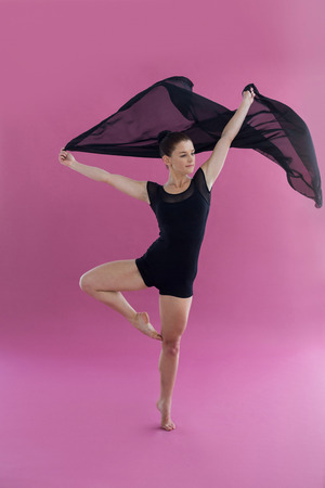 Dancer practicing contemporary dance against pink background