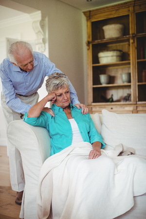 ageing process: Senior man comforting senior woman in living room at home Stock Photo
