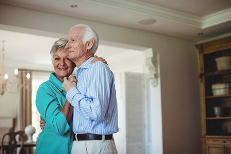 Senior couple dancing together in living room at home
