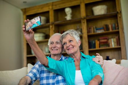 ageing process: Senior couple taking a selfie on mobile phone in living room at home Stock Photo