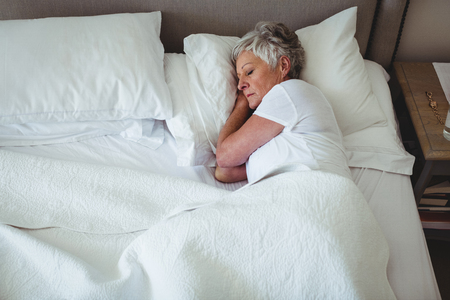 ageing process: Senior woman sleeping on bed in bedroom at home Stock Photo