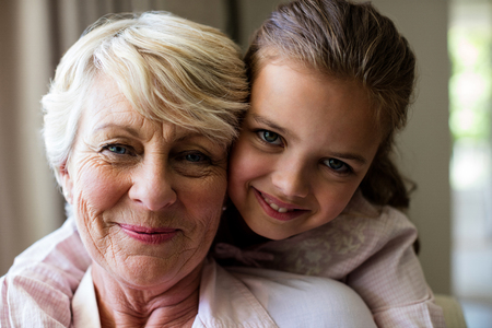 Portrait of granddaughter embracing her grandmother at home Stock Photo
