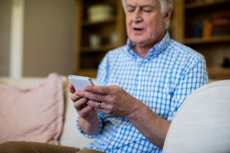 ageing process: Senior man using mobile phone in living room at home Stock Photo