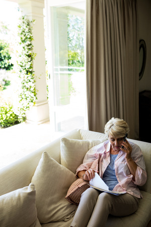 house call: Senior woman talking on mobile phone while checking a document in living room at home Stock Photo