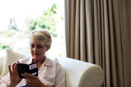Senior woman using mobile phone in living room at home Stock Photo