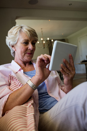 ageing process: Senior woman using digital tablet in living room at home Stock Photo