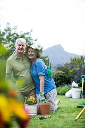 Portrait of senior couple embracing each other while gardening in lawn