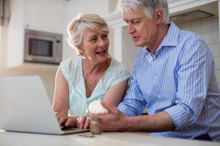 Senior couple checking medicine on laptop in kitchen at home