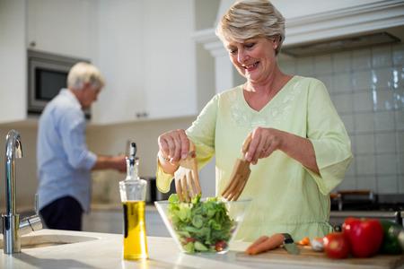 Senior woman preparing vegetable salad in kitchen