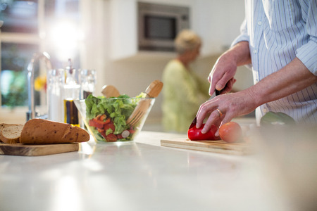 domicile: Close-up of senior man cutting vegetables for salad in kitchen Stock Photo