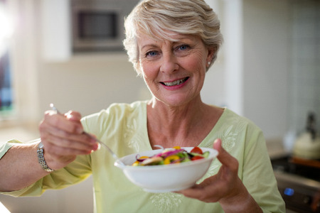 Senior woman holding vegetable salad in bowl in kitchen