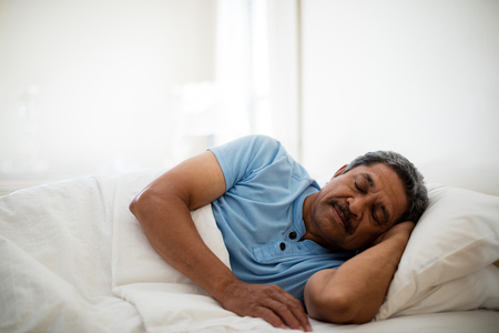 Senior man resting on bed in bedroom at home