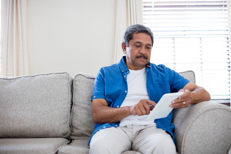 Senior man using digital tablet in living room at home