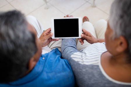 pc screen: Senior couple using digital tablet while sitting in the living room at home