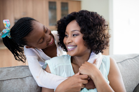 Mother and daughter embracing each other in living room at home