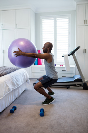 Man Exercising With Fitness Ball In Bedroom At Home Stock Photo   69604594