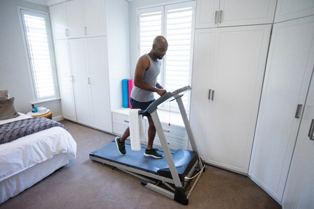 Mid section of man using smart watch while exercising on treadmill at home