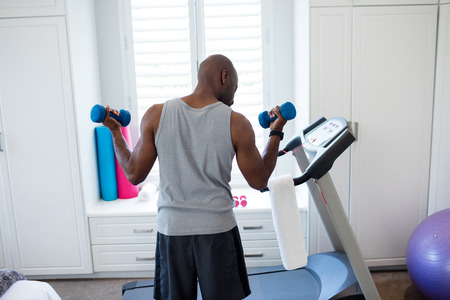 Rear View Of Man Exercising With Dumbbells In Bedroom At Home Stock Photo    69604615