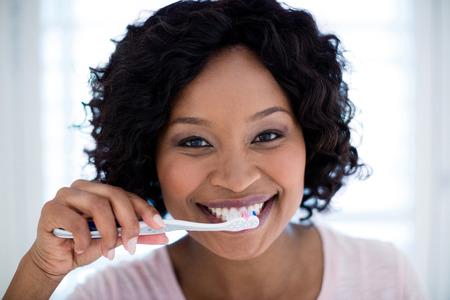 Portrait of woman brushing her teeth Stock Photo