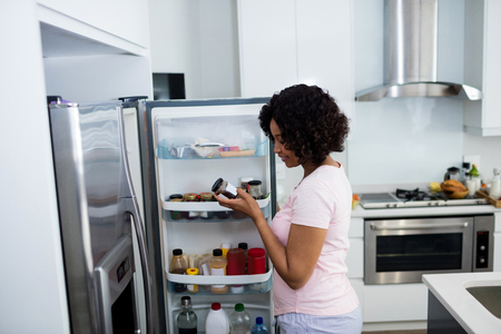 apartment search: Woman removing bottle from refrigerator in kitchen at home Stock Photo