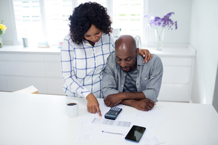 Couple checking bill in kitchen at home Stock Photo