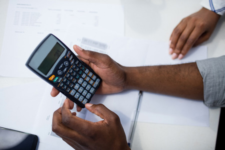 checking account: Close-up of mans hand using a calculator at home Stock Photo