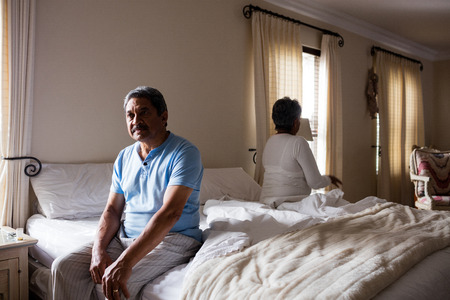 ignoring: Upset senior couple ignoring each other in bedroom at home Stock Photo