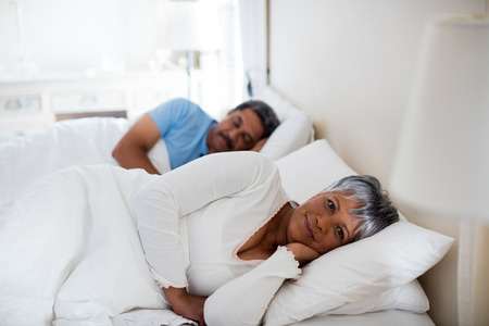 ageing process: Portrait of senior woman relaxing on bed in bedroom at home Stock Photo