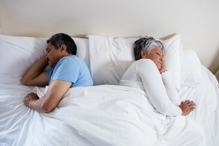ageing process: Senior couple sleeping together on bed in bedroom at home