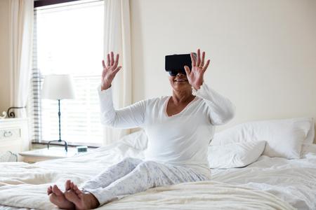 Senior woman using virtual headset on bed in bedroom