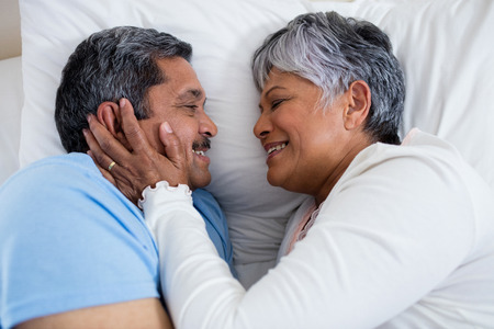 ageing process: Senior couple relaxing together on bed in bedroom at home Stock Photo