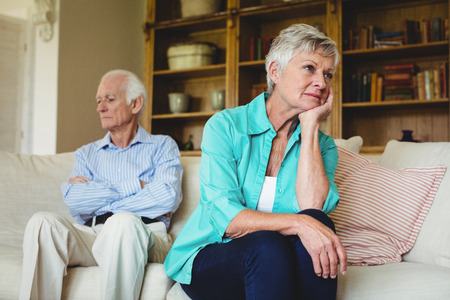 ignoring: Upset senior couple ignoring each other in living room at home