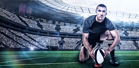 kick around: Portrait of rugby player in black jersey placing ball against rugby stadium with copy space 3d Stock Photo
