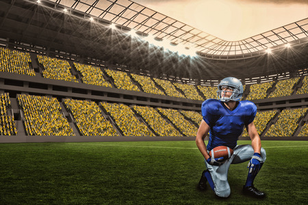 paraplegico: American football player with ball kneeling against large football stadium with fans in yellow with copy space 3d