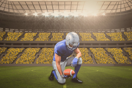 American football player kneeling while holding ball against large football stadium with fans in yellow with copy space 3d
