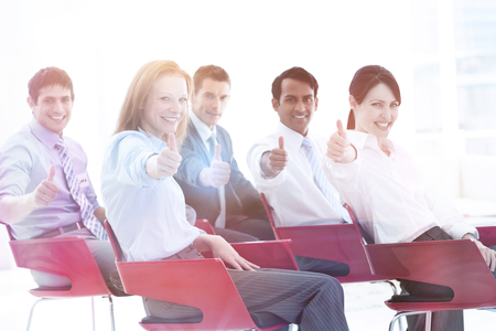 Business people with thumbs up at a conference. Business concept.