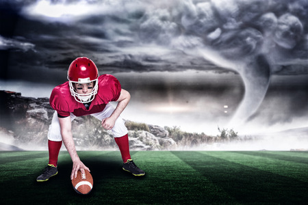 American football player in attack stance against stormy sky with tornado over landscape with copy space 3d Stock Photo