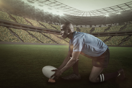 kick around: Confident rugby player looking away while keeping ball on kicking tee against rugby stadium with copy space  3d