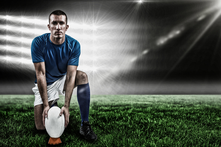 Full length portrait of rugby player placing ball against spotlightand copy space 3d Stock Photo