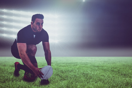 kick around: Rugby player getting ready to kick ball against spotlight and copy space 3d
