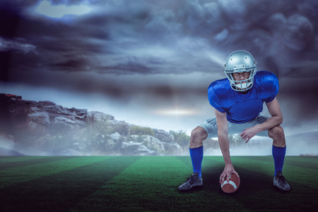 American football player placing ball against stormy sky with tornado over landscape with copy space 3d Stock Photo