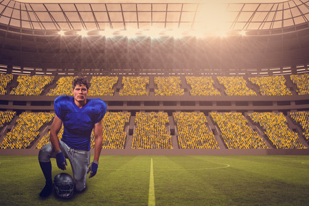 Portrait of confident American football player holding helmet while hand on knee against large football stadium with fans in yellow with copy space 3d