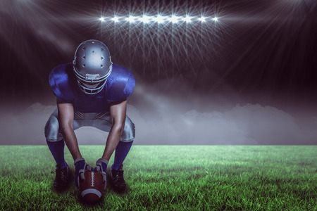 American football player in uniform holding ball while crouching against spotlight with copy space 3d