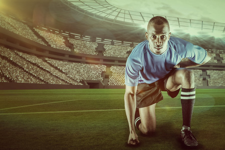 kick around: Portrait of confident sportsman kneeling against rugby stadium with copy space 3d Stock Photo