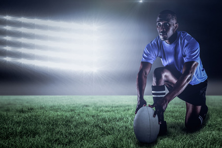 Rugby player holding ball while kneeling against spotlight and copy space 3d