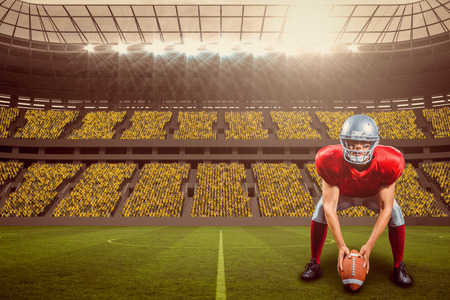American football player placing ball while playing against large football stadium with fans in yellow with copy space 3d Stock Photo